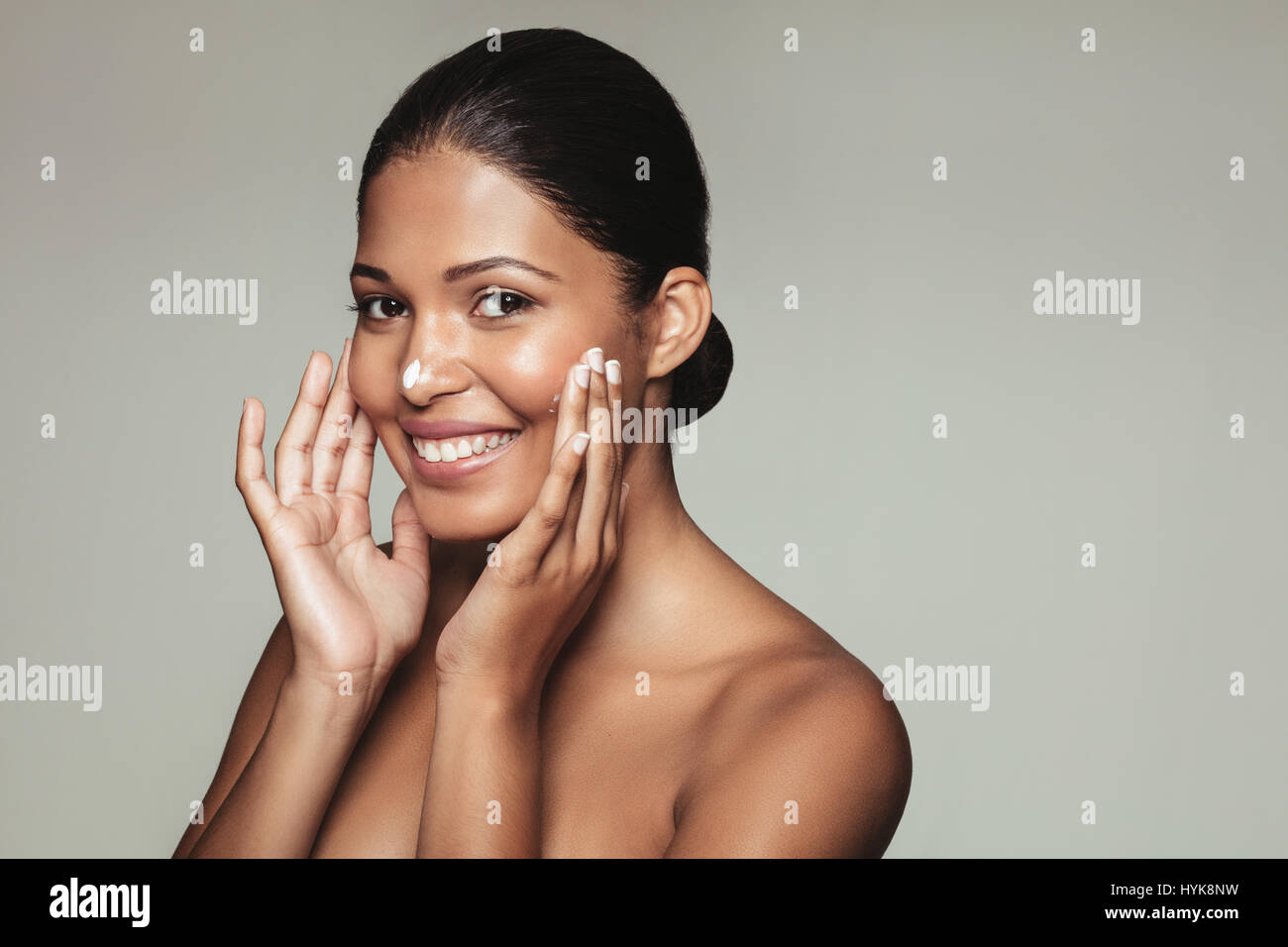 Close up portrait of pretty young woman applying cream to her face. Smiling female model with healthy skin applying - Stock Image