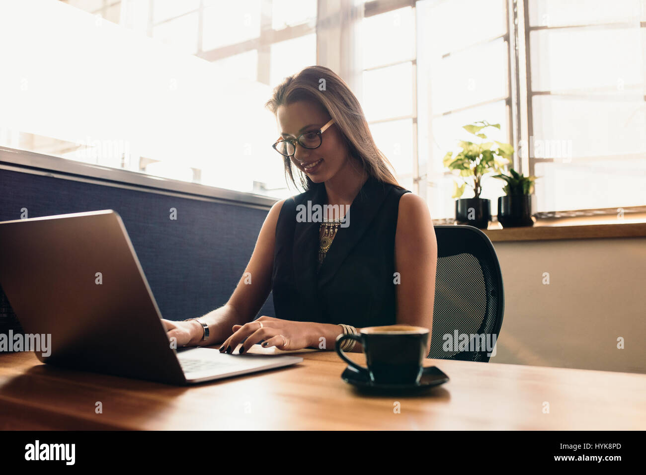 Female vlogger editing her vlog on Computer. Young woman at her desk in office working on computer with a cup of - Stock Image
