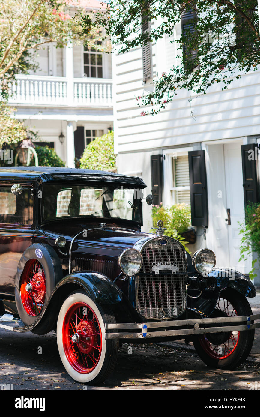 A black Ford 1928 Model A with red wheels parked in front of a white house and black shutter colonial home in historic Stock Photo