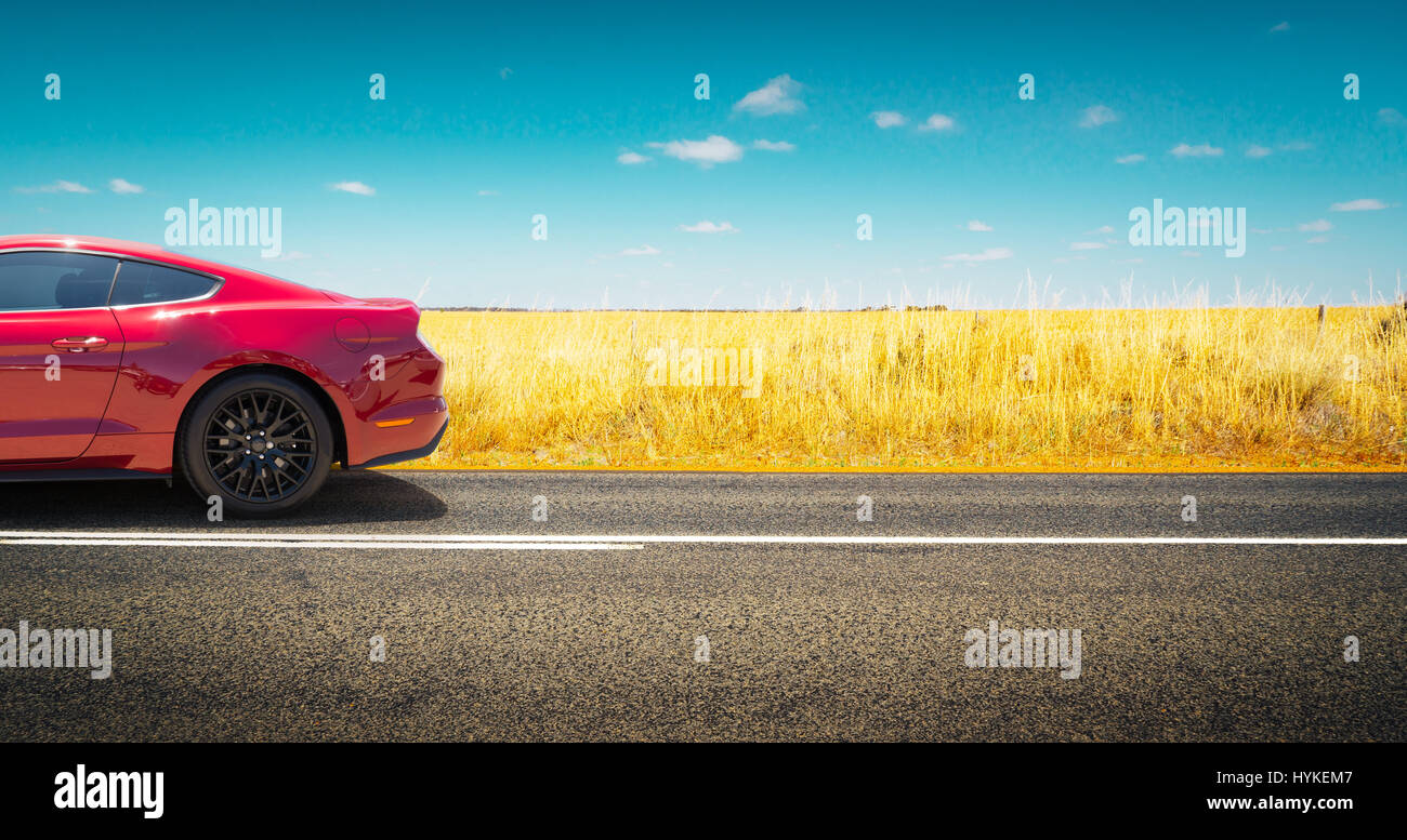 Sport car  parked on road side with field of golden wheat background . - Stock Image