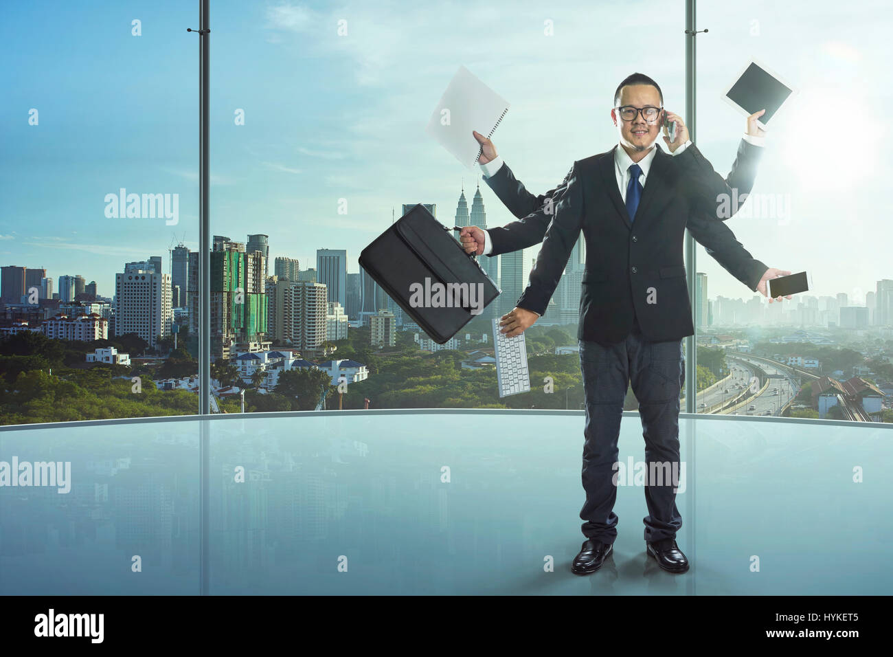 The businessman has a lot of hands to complete his work, a powerful businessman concept. - Stock Image