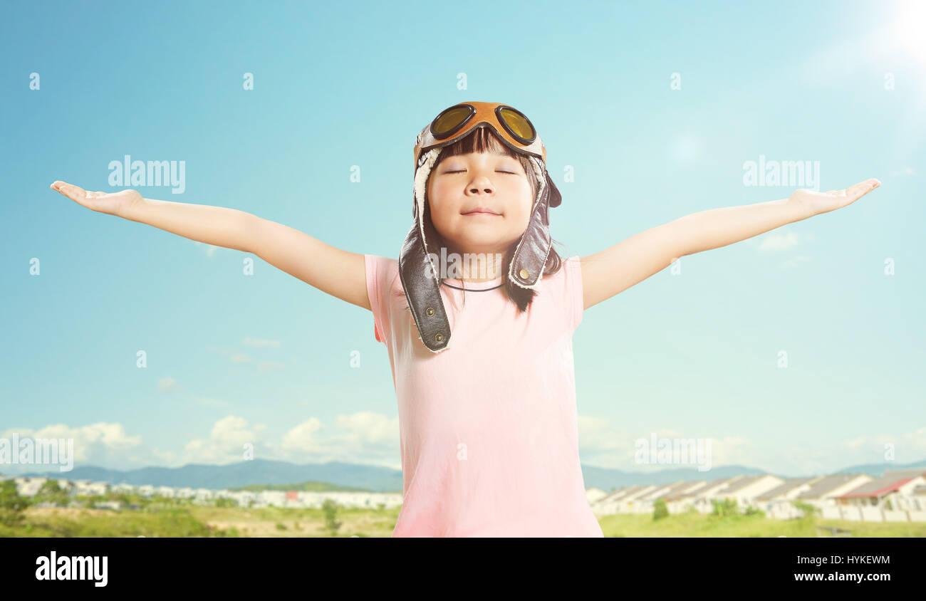 Little asian girl wear aviator glasses and enjoy her travel dreams , summer sky background . - Stock Image