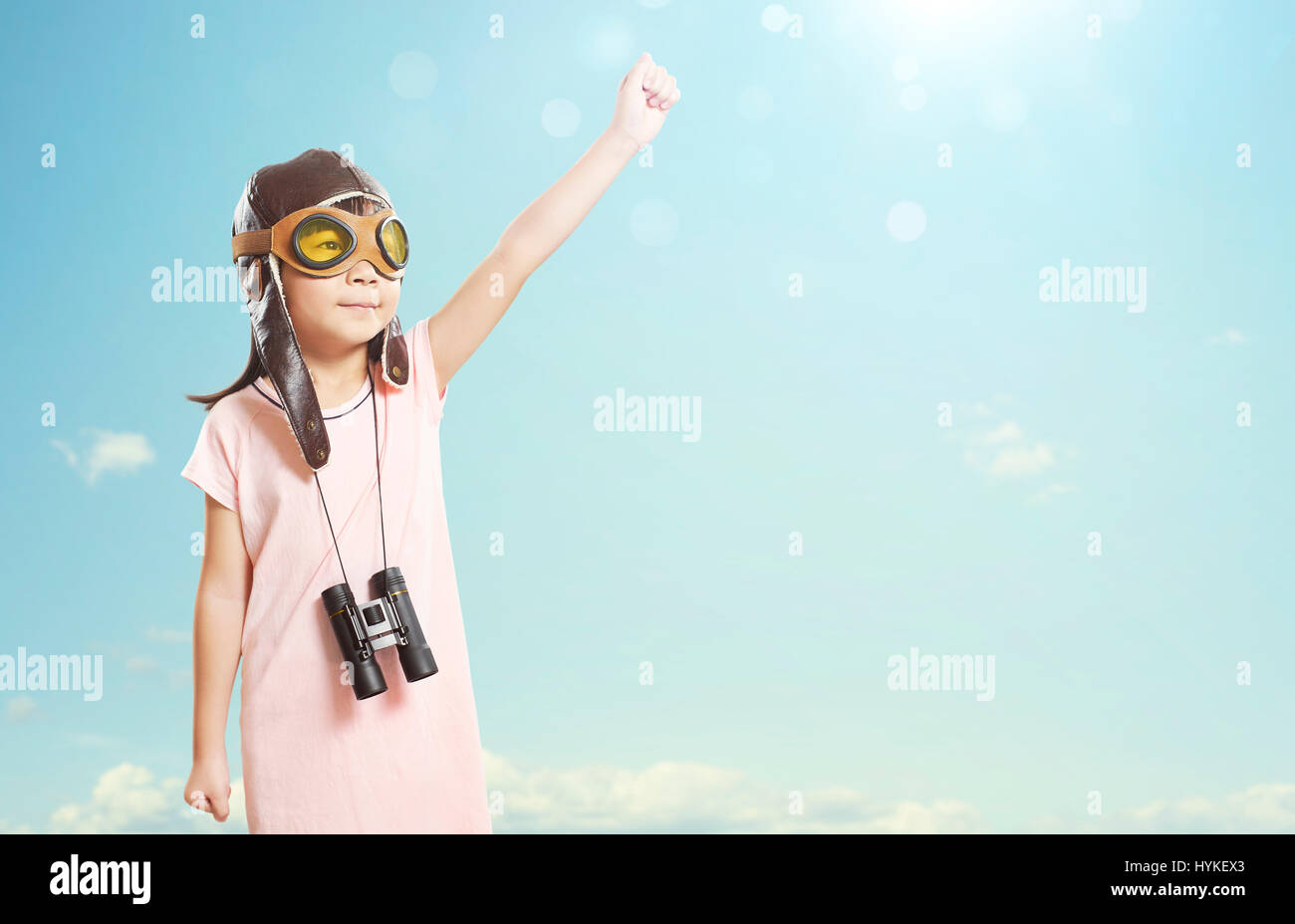 Little asian girl wear aviator glasses,telescope and enjoy her travel and adventure dreams , summer sky background - Stock Image