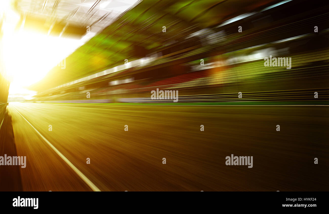 Foward motion speed lens blur racing circuit background with seated stand , sunset scene  . - Stock Image