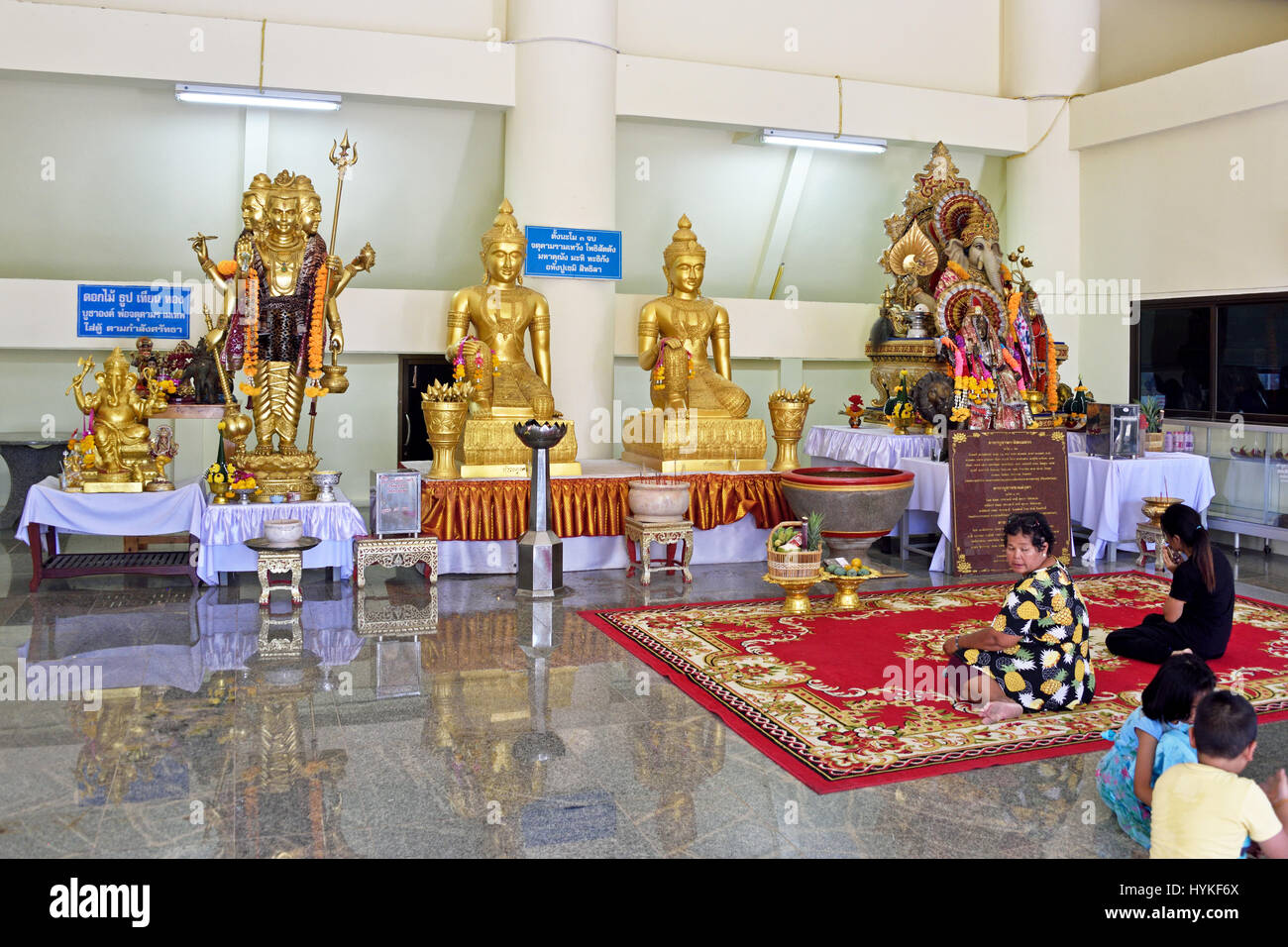 Worshippers in the hall beneath the large pink elephant in Wat Phrong Akat in Bang Nam Priao District in Central - Stock Image