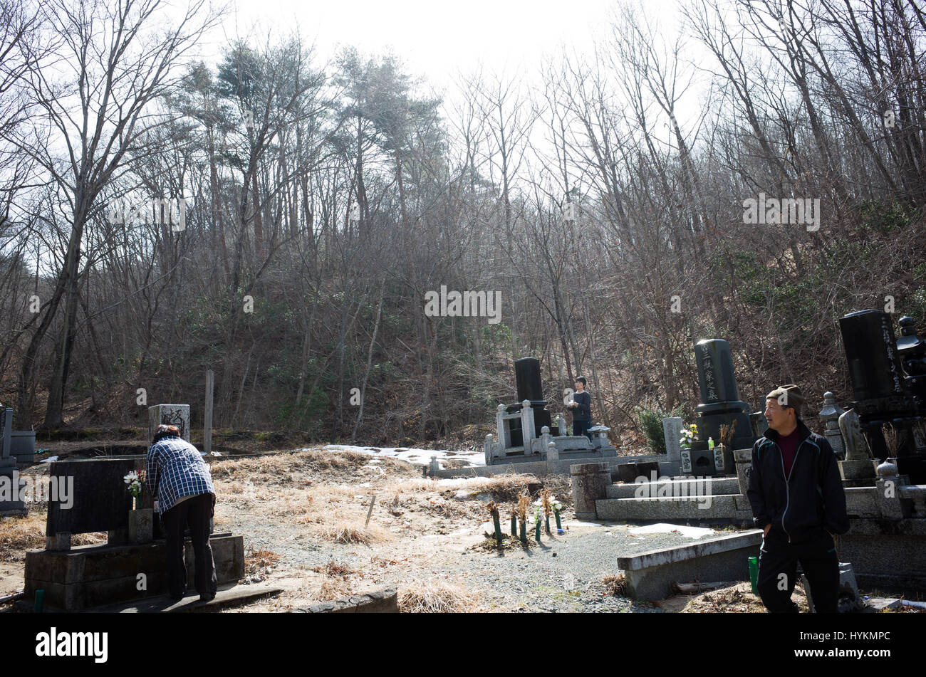 OTAMA VILLAGE, FUKUSHIMA: Toshinori and Keiko at a cemetery. ONE FAMILY'S five-year struggle to overcome the Fukushima - Stock Image