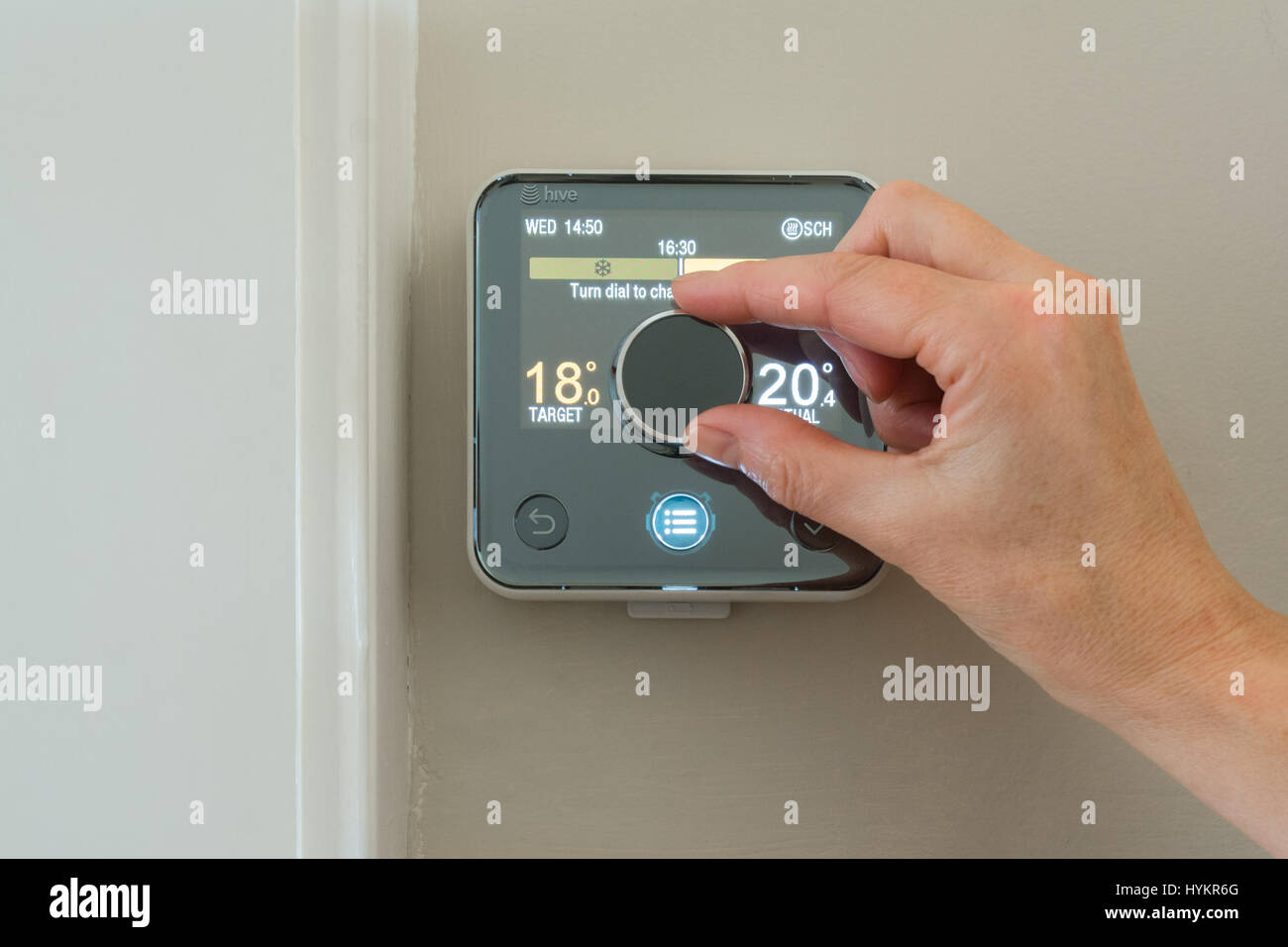 Hive heating thermostat being turned down by female hand - Stock Image