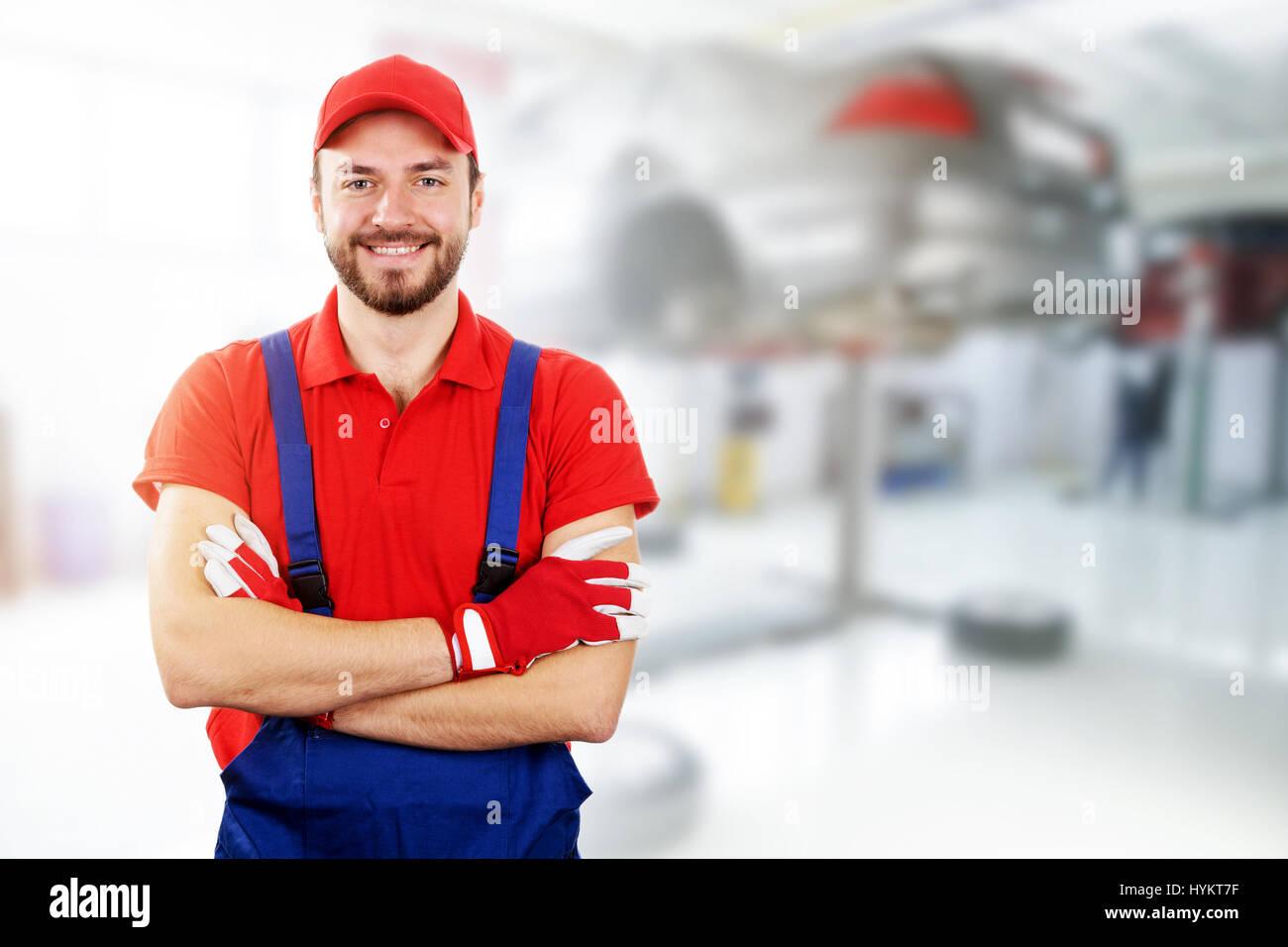 happy auto mechanic standing in car service garage - Stock Image