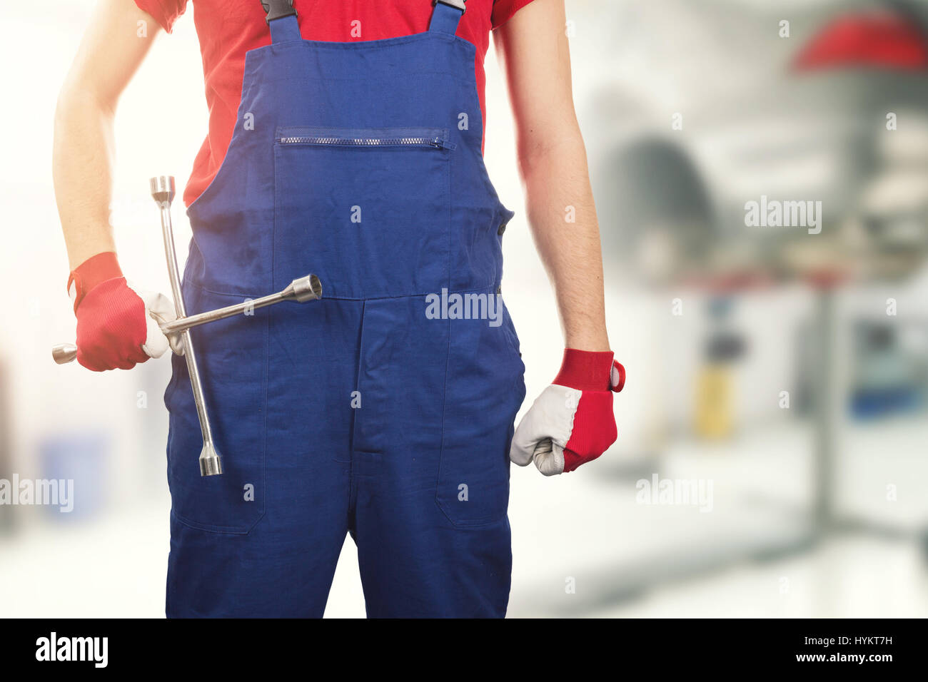 auto mechanic with tire wrench in hand in car service - Stock Image