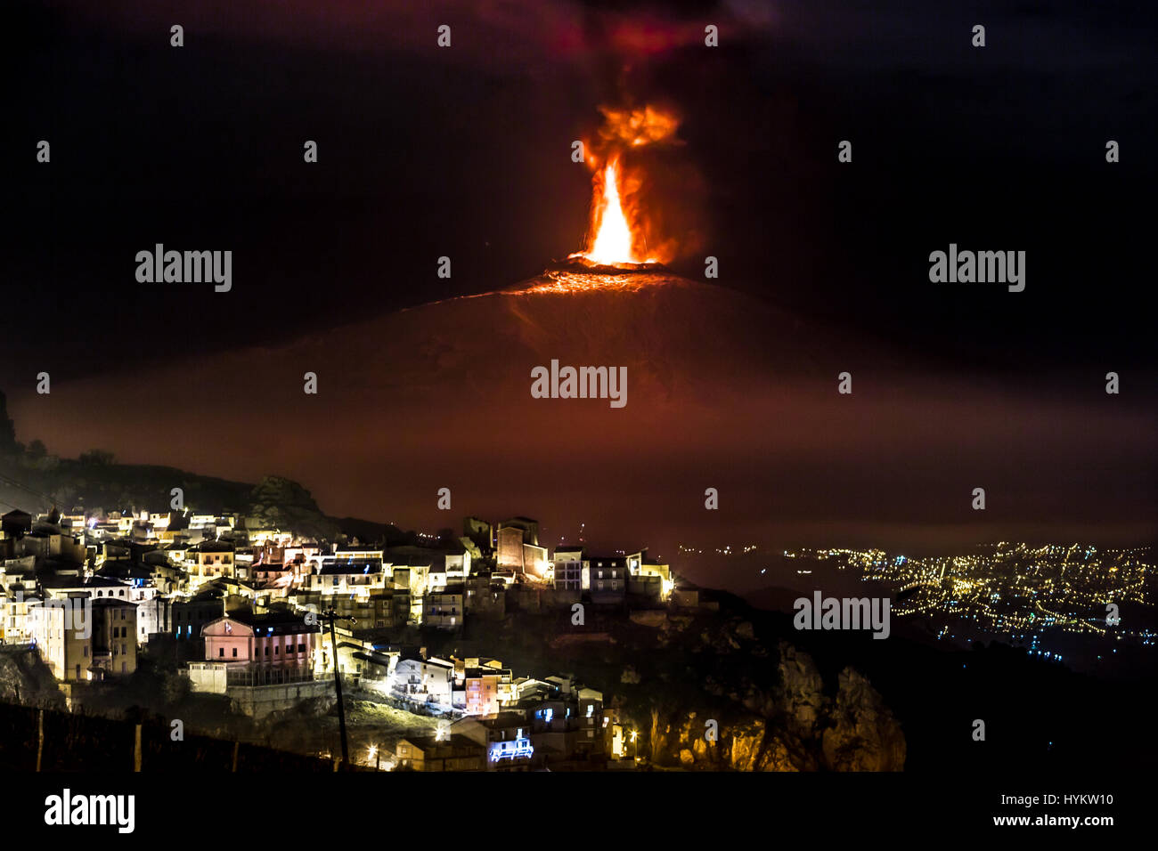 MESSINA, SICILY: A night picture of an eruption at Mount Etna. A NUCLEAR mushroom-like cloud blasting from Mount Etna in Sicily have been captured by an astonished local man. Roaring flames and huge plumes of smoke can be seen pumping out of the top of one of the world's most active volcanoes.  Pictures show how the residents of Sicily live in the shadow of this monster mountain, which measures eleven thousand feet in height and is where the ancient Roman god of fire, Vulcan built his workshop. Agriculture Officer Fernando Famiani (51) from San Teodoro, Messina in Sicily snapped the imposing M Stock Photo