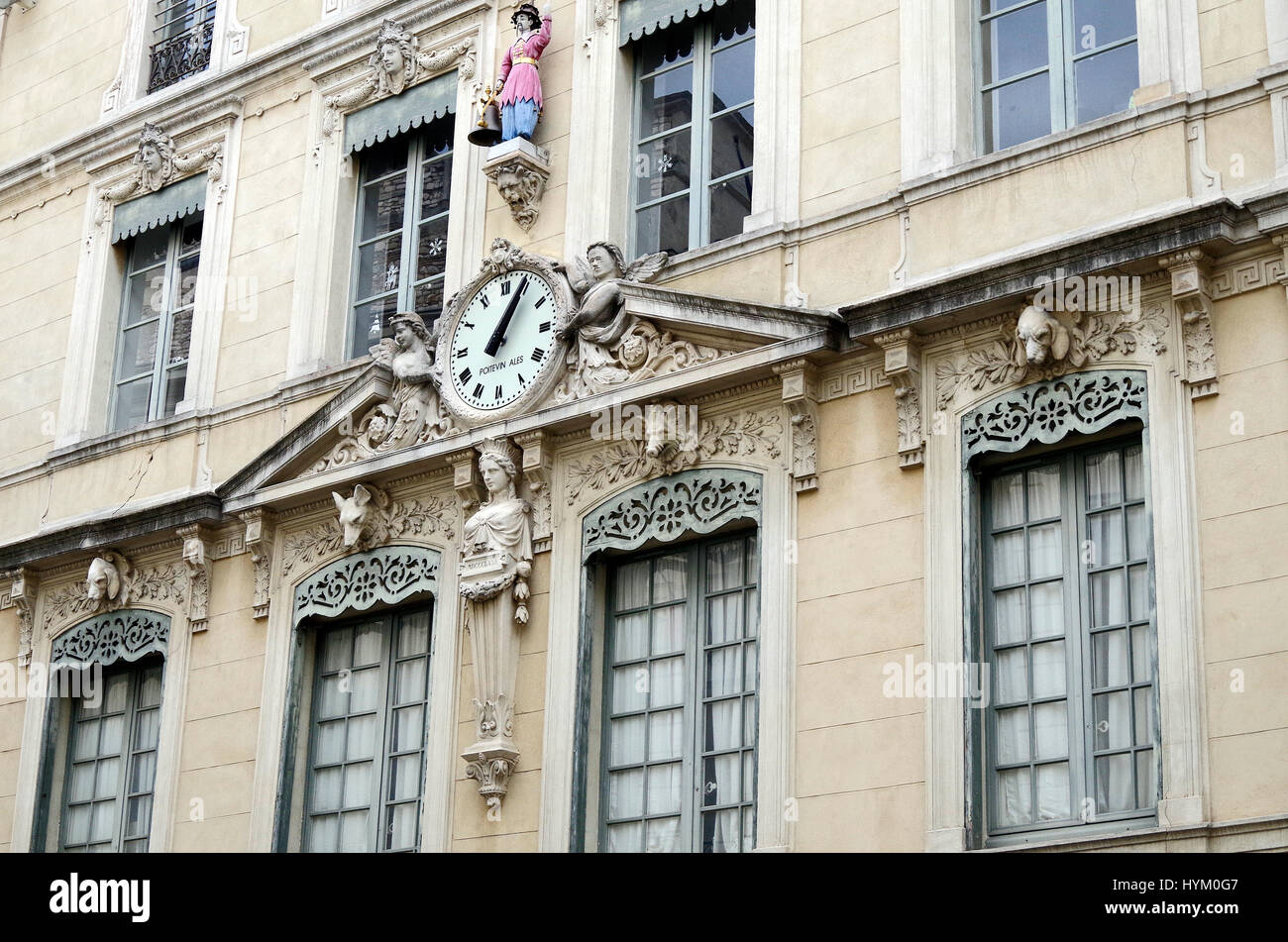 Detail of elegant building in the Place de la Hotel de Ville in Nimes, France, with a black-hatted,  pink-jacketed - Stock Image