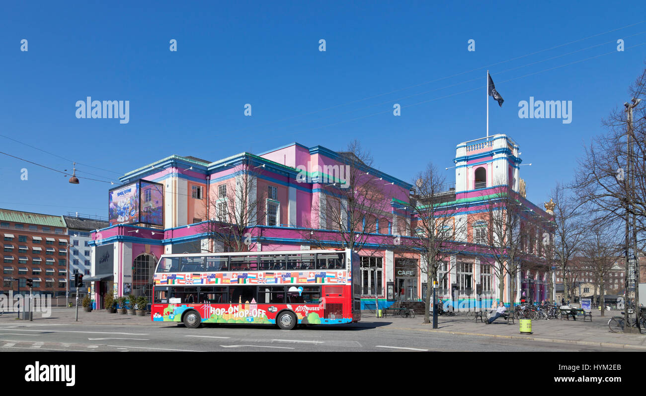 A Hop on hop off tourist bus in front of the colourful and historic Palads building in Copenhagen on a sunny spring - Stock Image