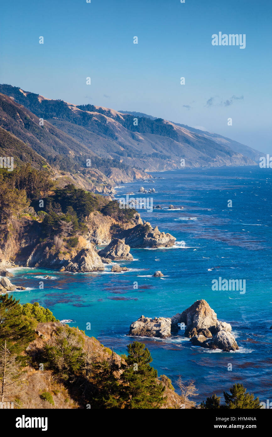 Rugged coastline of Big Sur with Santa Lucia Mountains along famous Highway 1 illuminated in beautiful golden evening - Stock Image