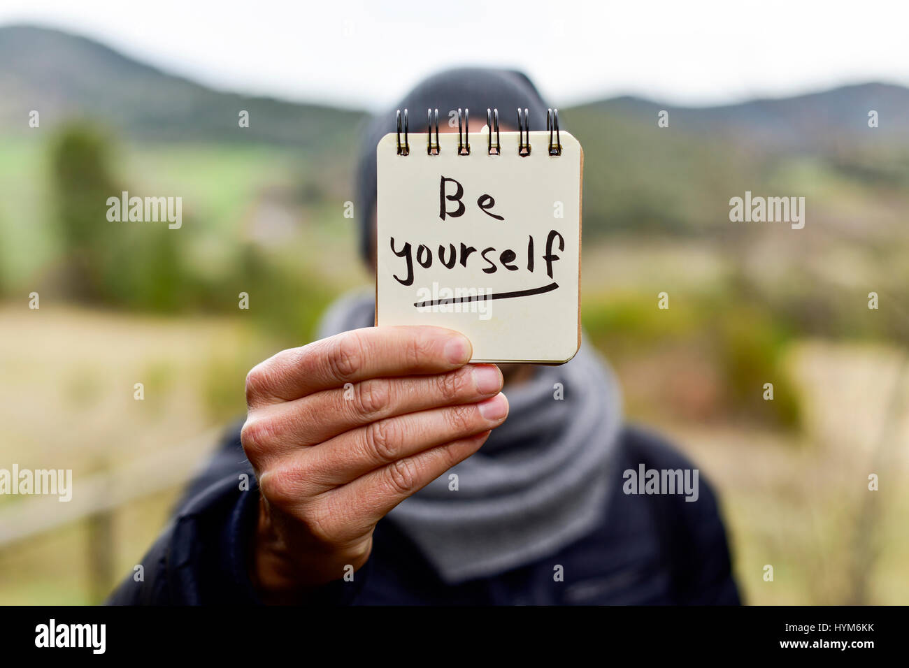 closeup of a young caucasian man wearing a scarf and a knit cap in a natural landscape showing a notepad with the - Stock Image