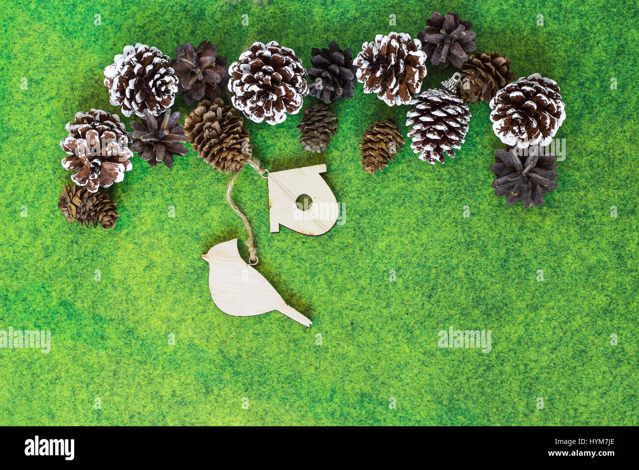 Pine and Fir cones with wooden ornaments on vibrant green felt background. Christmas greetings card background - Stock Image