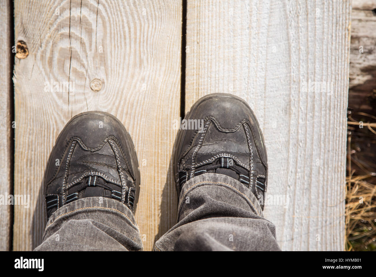 Two feet on a wooden footpath during the hiking in an early spring. - Stock Image