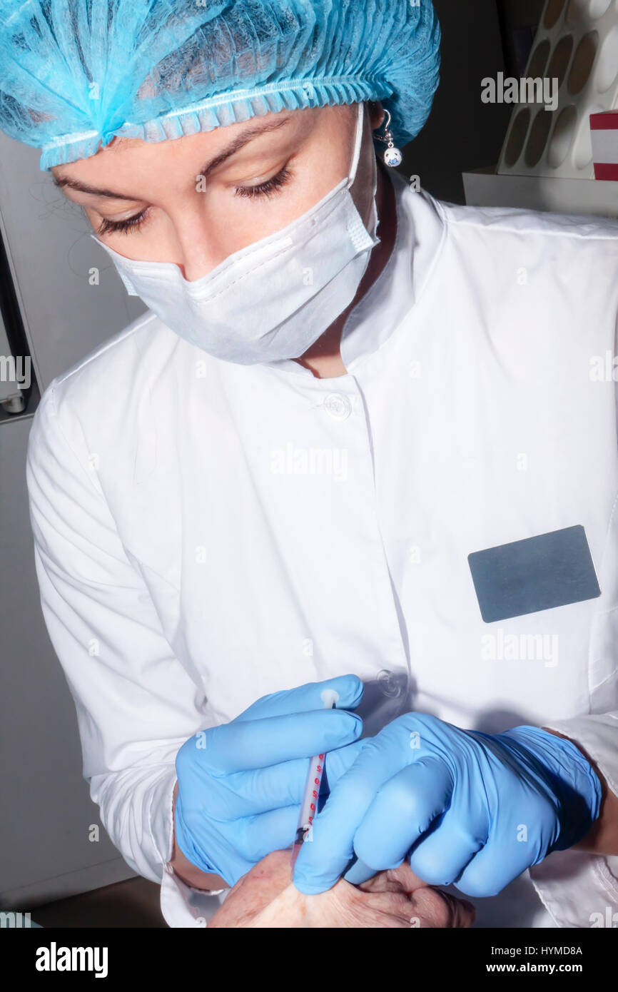 Microsurgery : Dermatologist performs local anesthesia on the hand Stock Photo