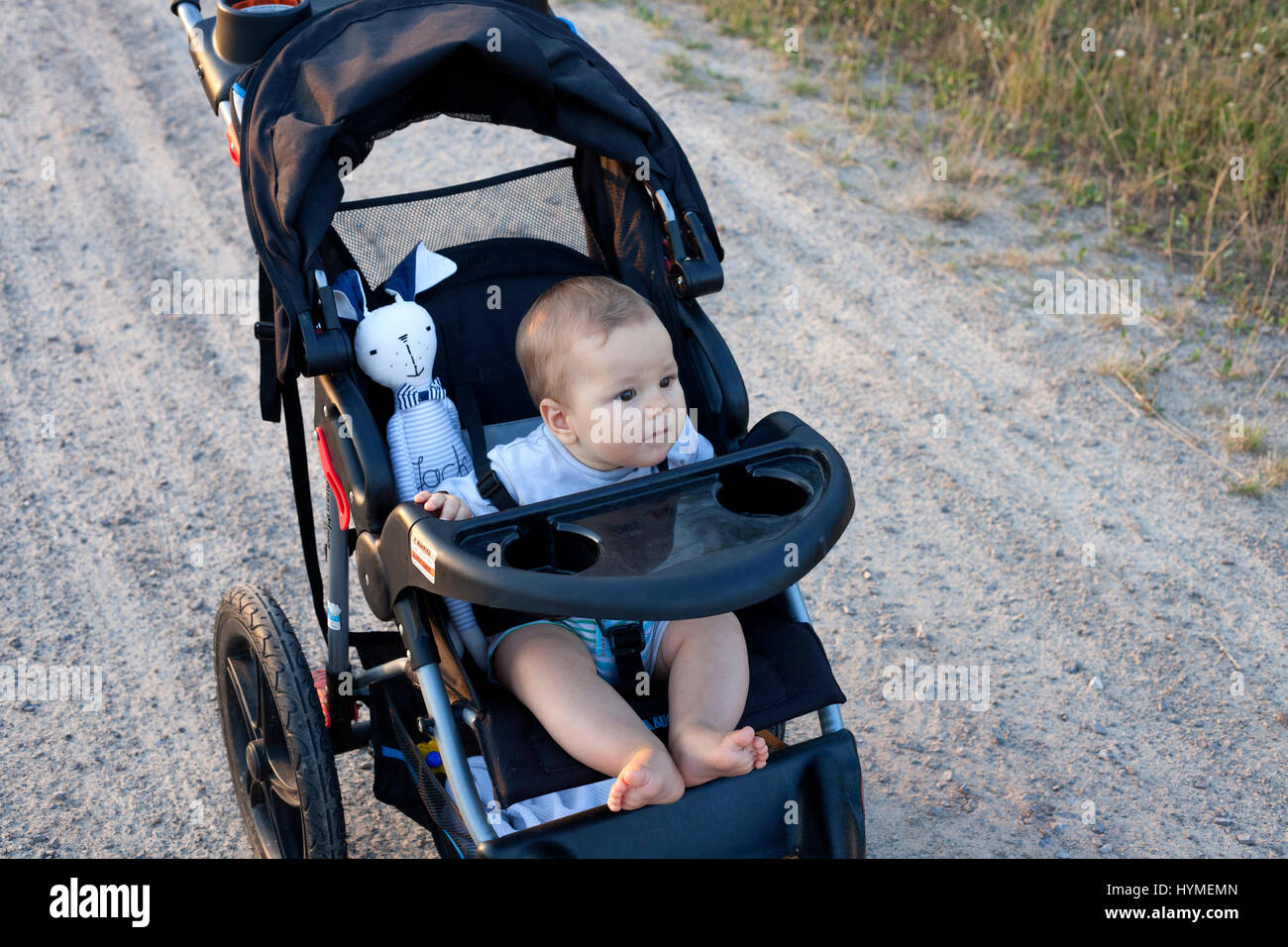 Alert barefooted infant baby taking a ride in his stroller. Polish Baby 7 months old. Zawady Central Poland Europe - Stock Image