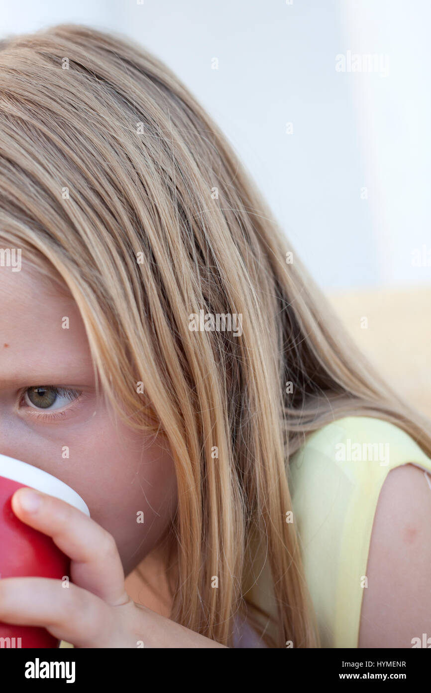 Absorbed girl age 8 drinking. Zawady Central Poland Europe - Stock Image