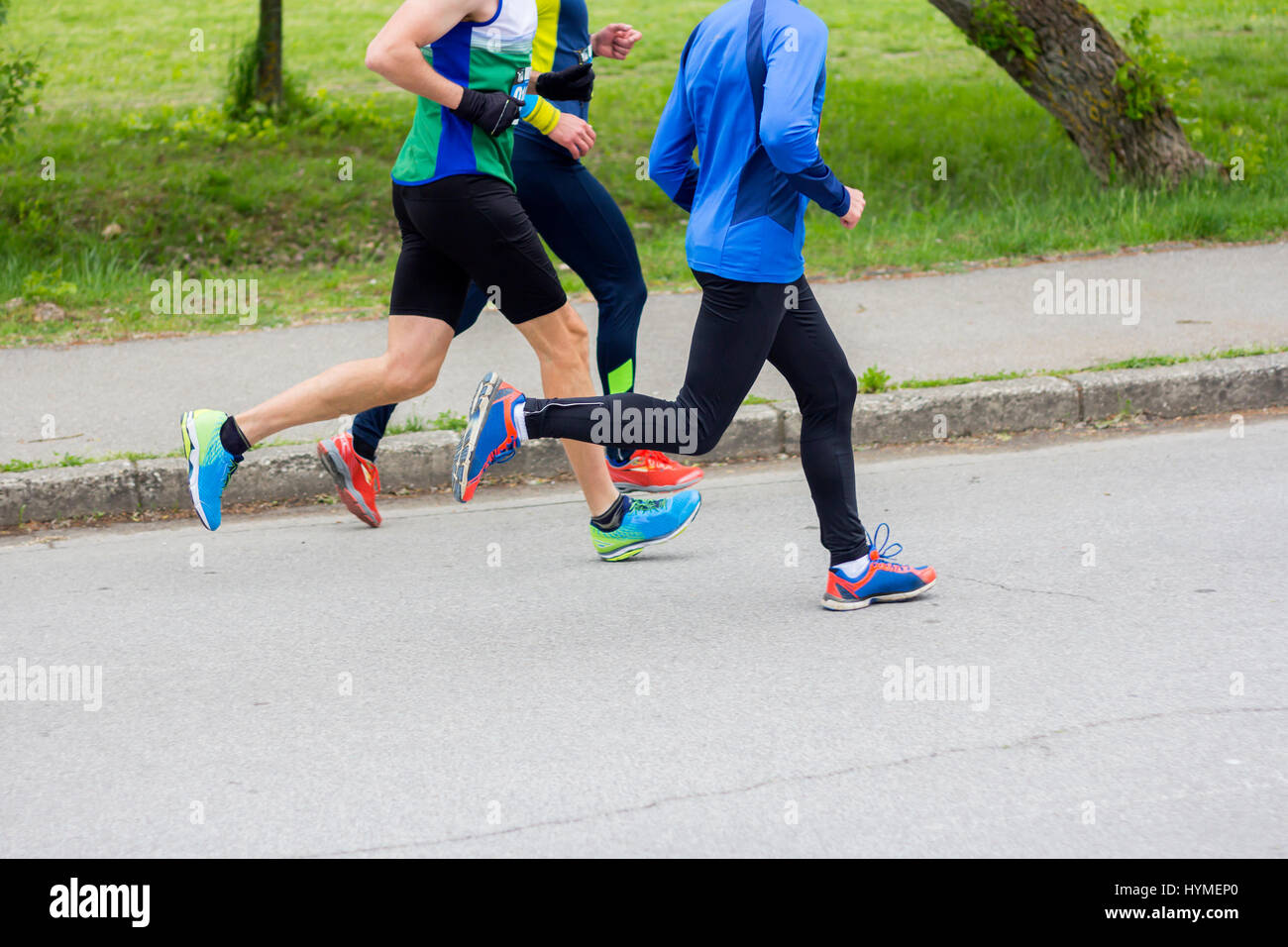 Marathon running race, three runners on city road - Stock Image