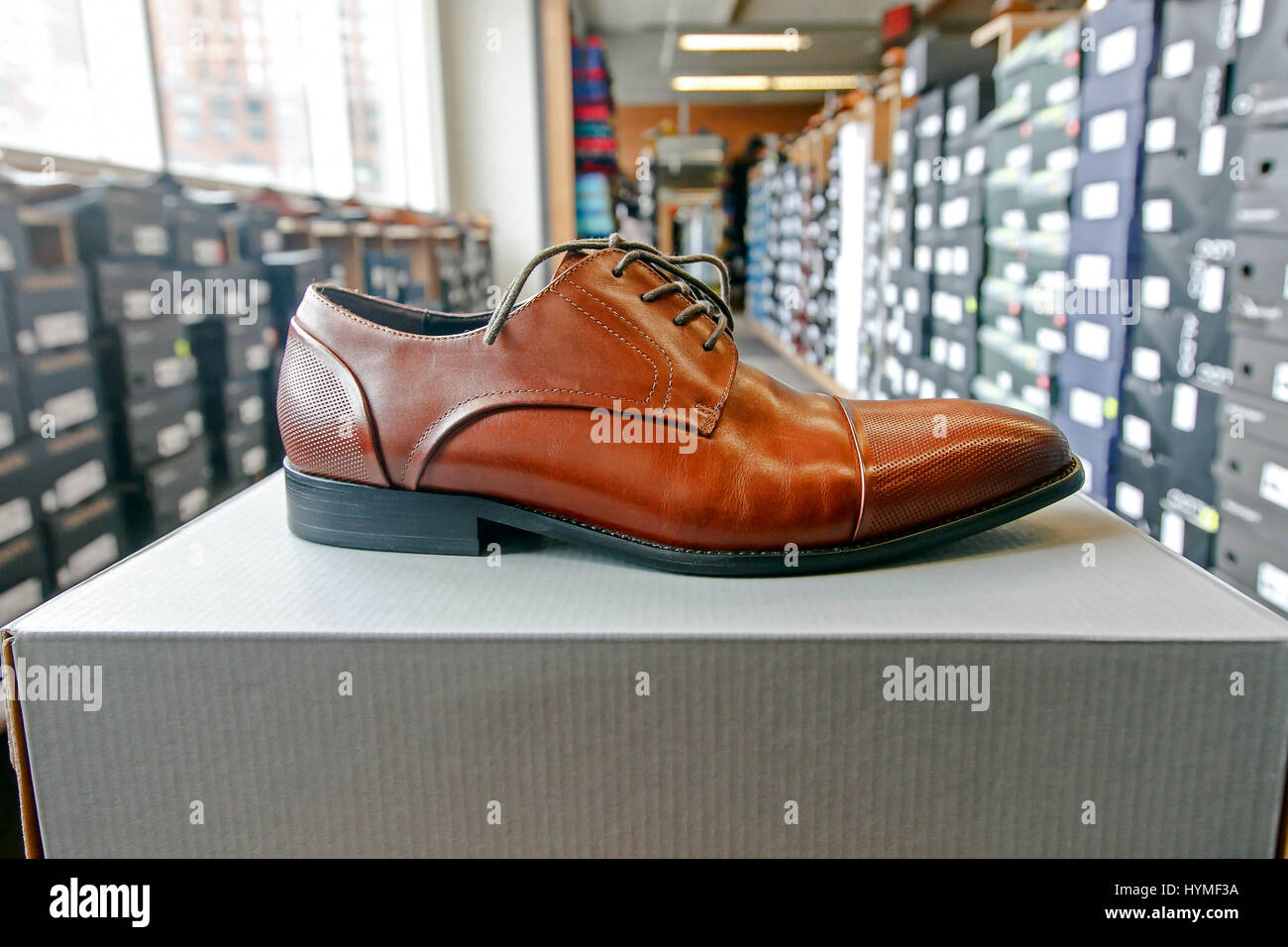 Mens dress shoe in a shoe store with stacks of boxes in the background. - Stock Image