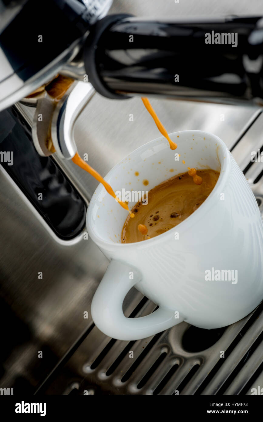 Traditional pump espresso coffee machine pouring shot into white cup - Stock Image