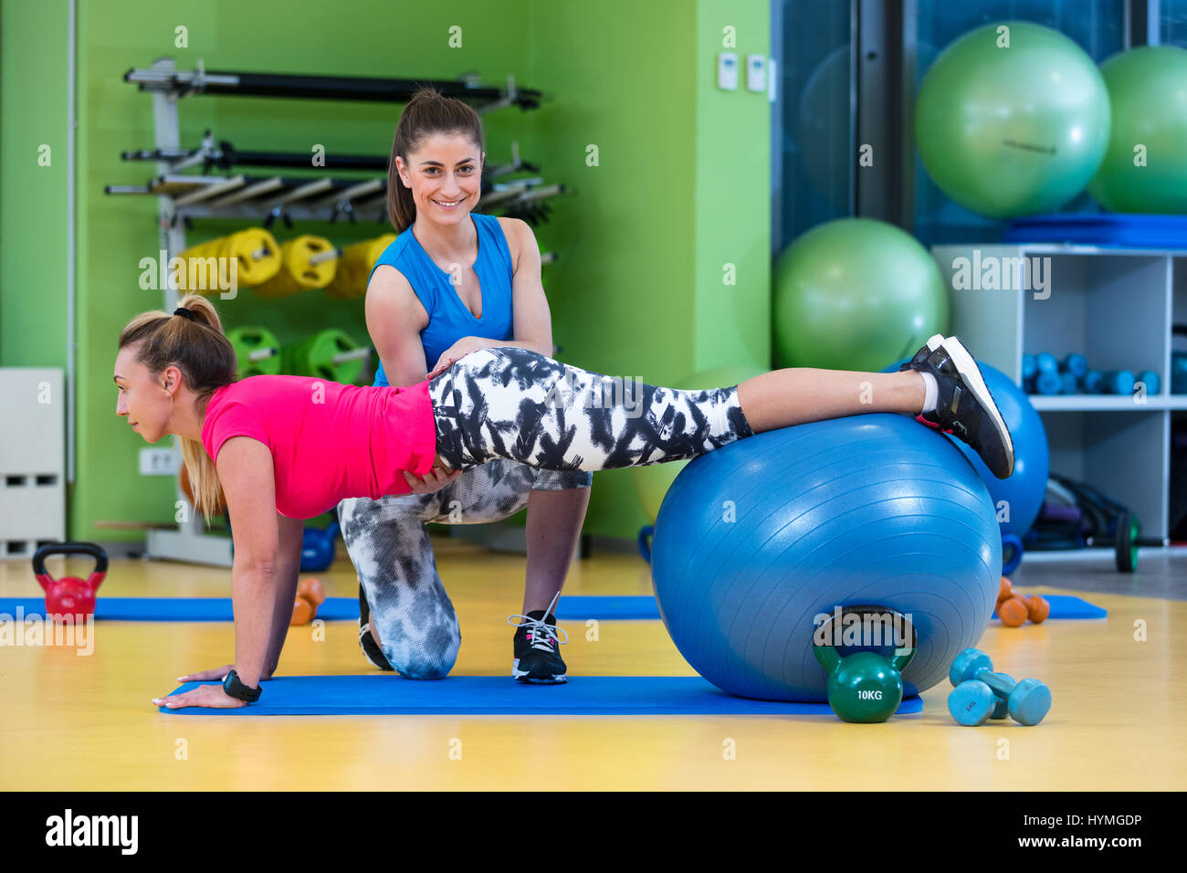 Trainer helping woman in doing exercise on ball - Stock Image