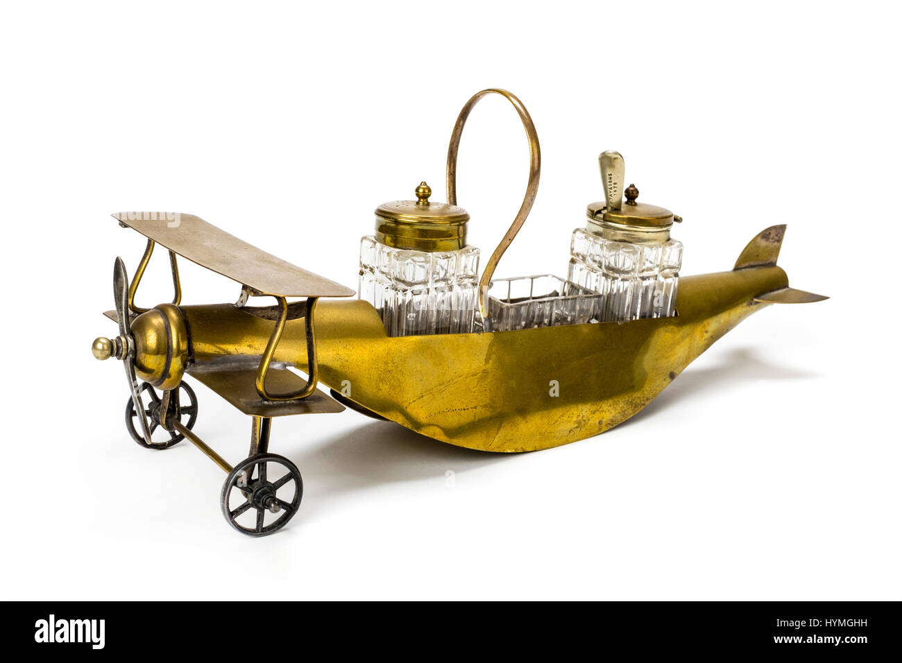 WW1 brass table condiment set in the form of a Royal Flying Corps bi-plane complete with cut glass salt and pepper - Stock Image