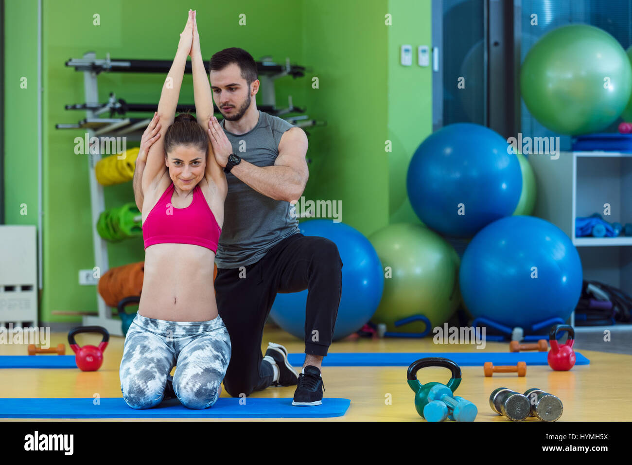 Young woman working out with personal trainer at the gym. Stock Photo