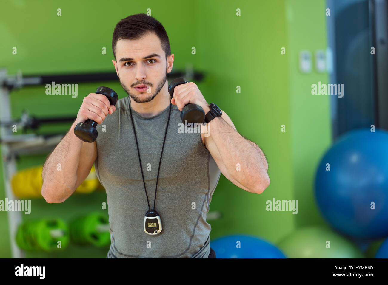 Young man lifting dumbbell at the fitness center - Stock Image