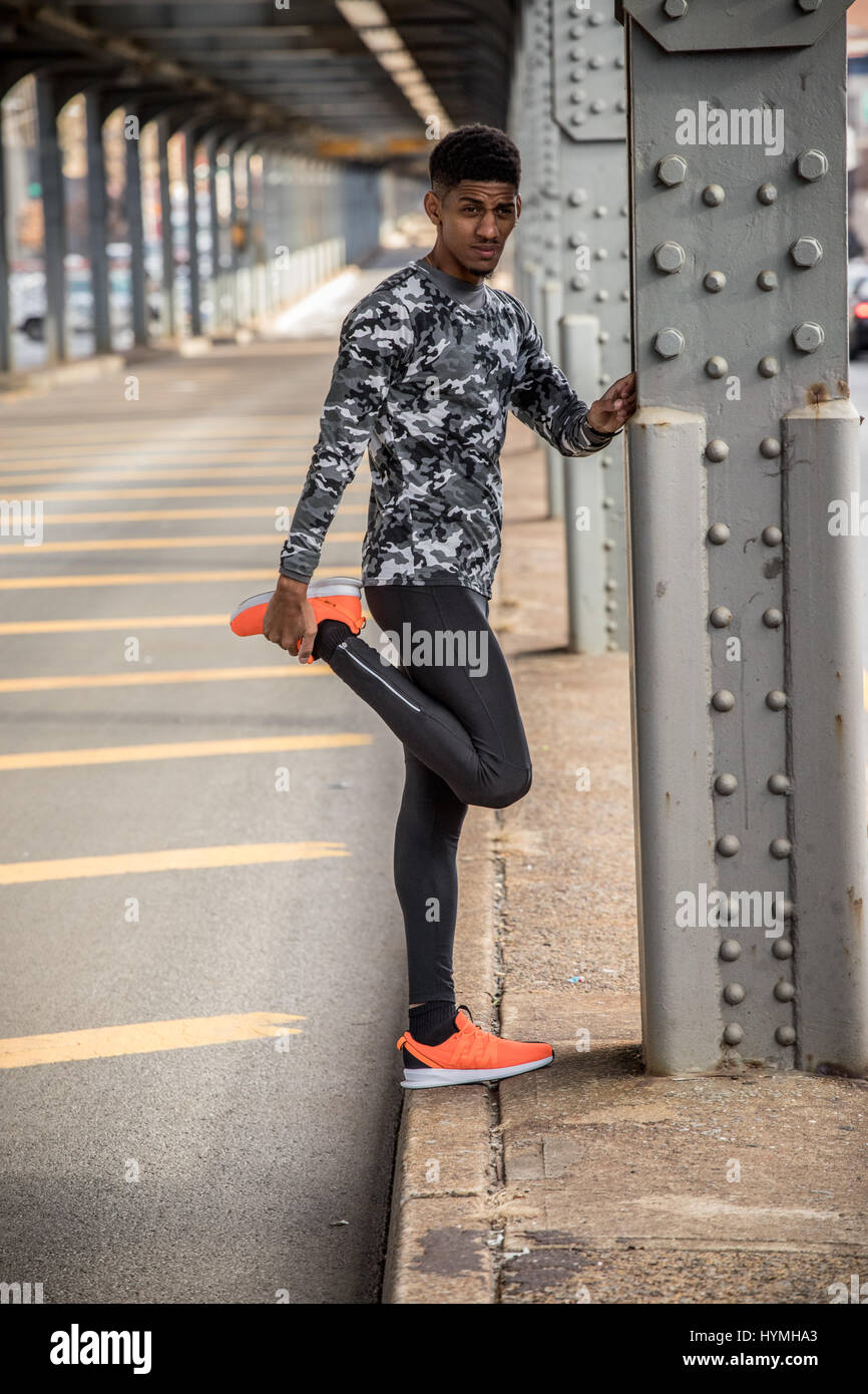 A young black man stretches to prepare for a run. Shot in Brooklyn, New York City during the Autumn of 2016. - Stock Image