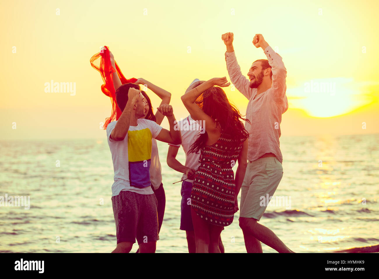 Young People Dancing On Beach at Sunset - Stock Image