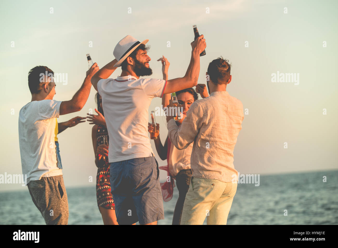 group of happy young people dancing at the beach on beautiful summer sunset - Stock Image