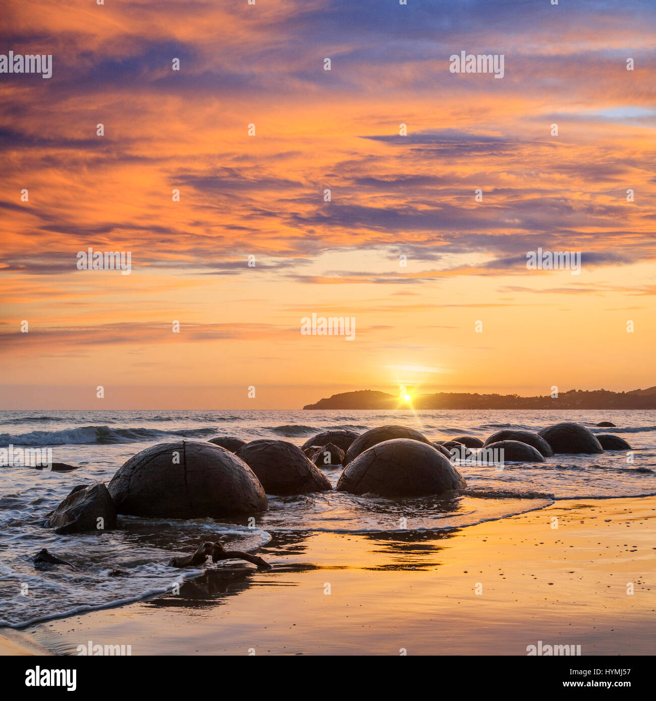 Sunrise at Moeraki Boulders, Otago, a major tourist attraction in the South Island of New Zealand. - Stock Image