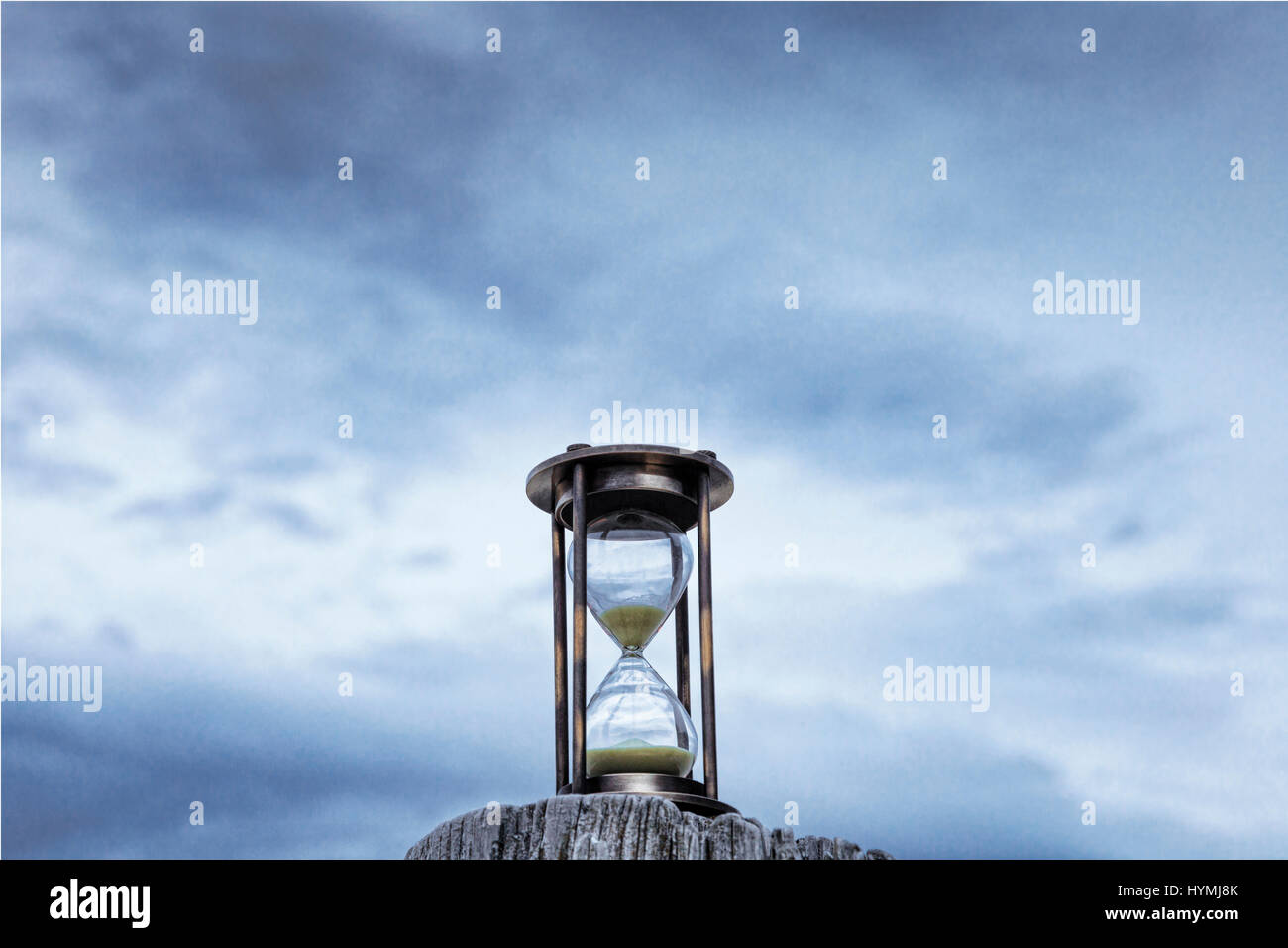 Hourglass or sand timer on a wooden post in front of a moody blue twilight sky. - Stock Image