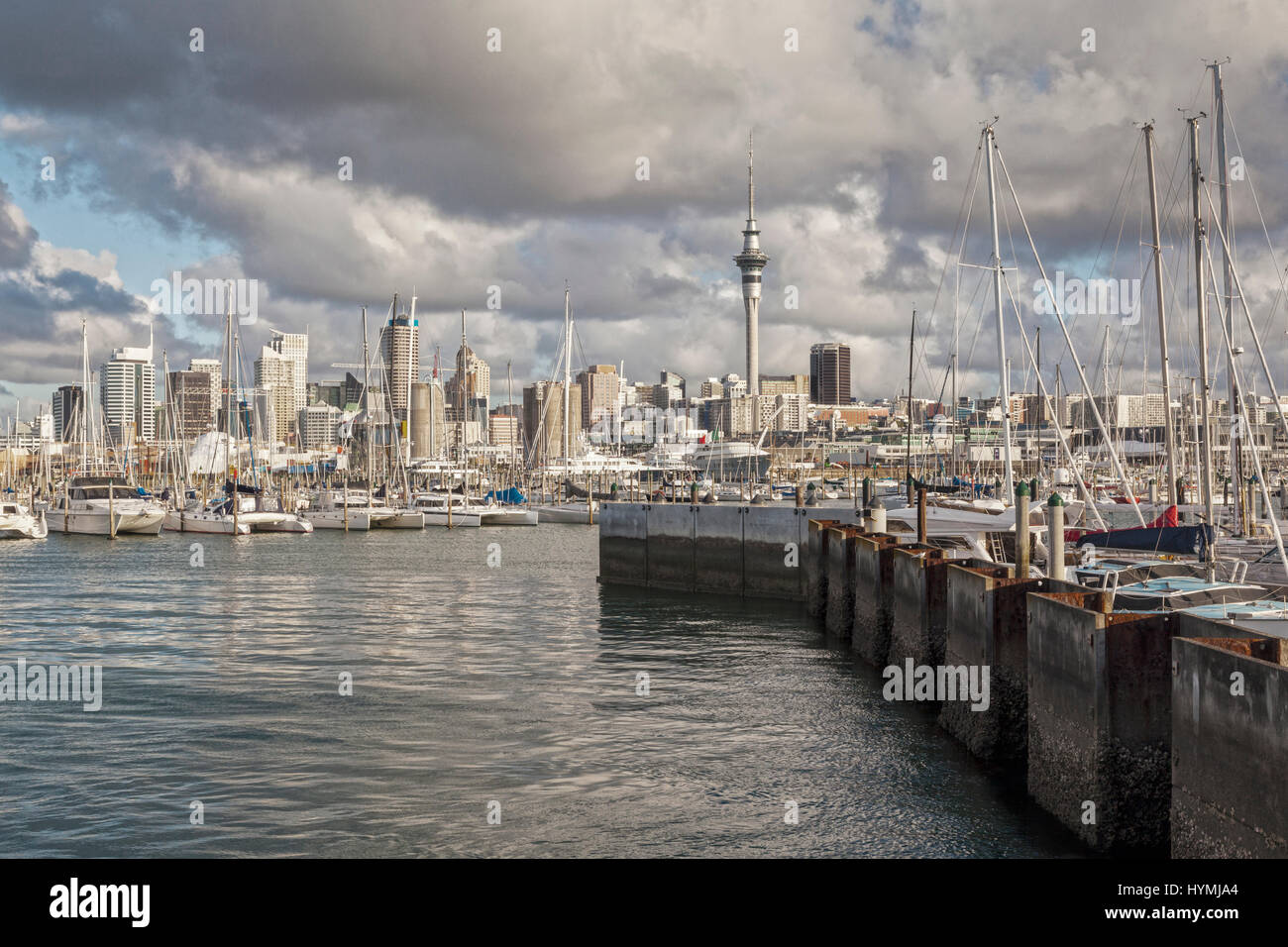 Auckland CBD and Westhaven Marina under a dramatic sunset sky. Stock Photo
