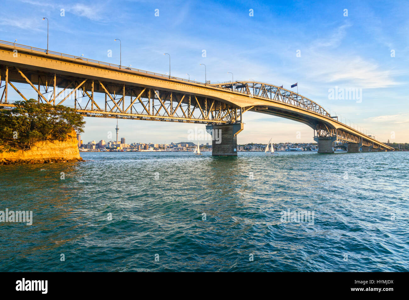Auckland Harbour Bridge in evening light with yachts passing under. - Stock Image