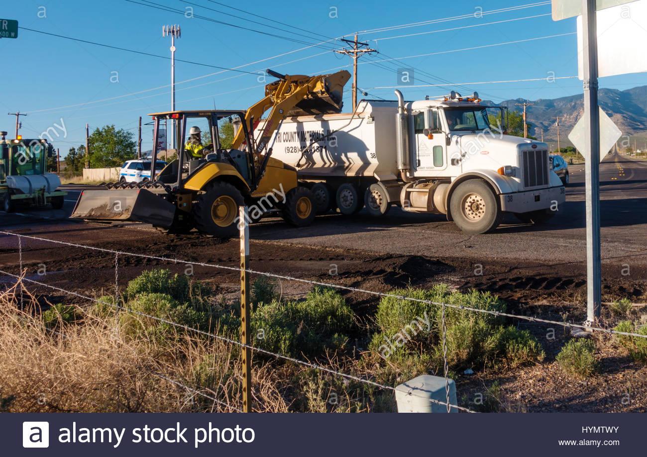 Caterpillar 415F2 loader loading dump truck on highway contruction job in Arizona  2 operators and truck driver - Stock Image