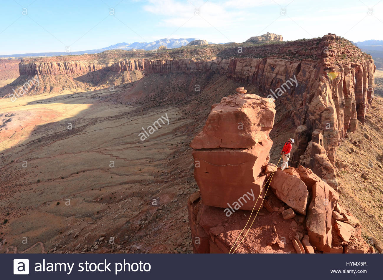 A man belays his climbing partner on Fisher Towers in Utah. - Stock Image