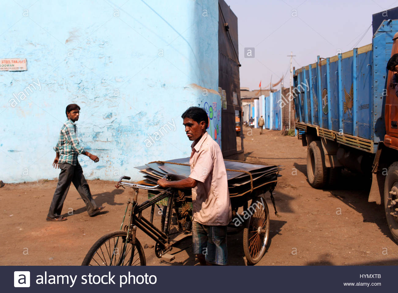 A man pushes a trickle carrying metal sheets in an industrial estate in Kolkata. - Stock Image