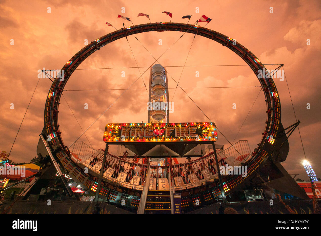 The Ring of Fire ride operates at the Iowa State Fair under dark storm clouds at sunset. - Stock Image