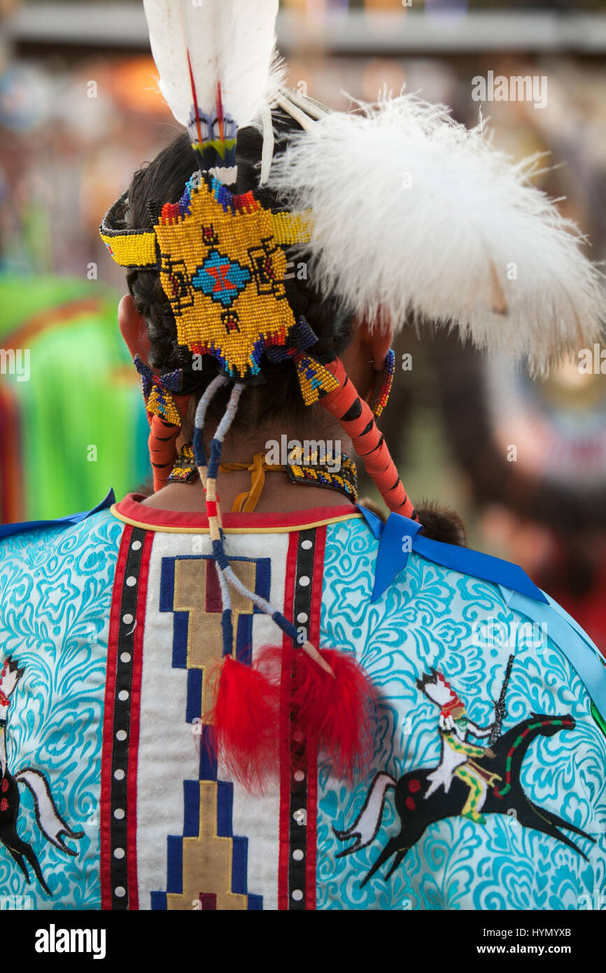 A woman wears traditional regalia for the annual pow wow at the Crow Indian Reservation. - Stock Image