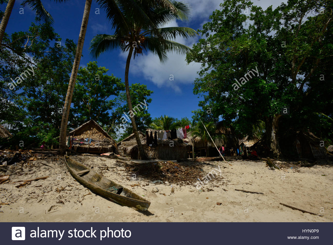 A beached canoe and local housing on a beach on Owaraha Island. - Stock Image