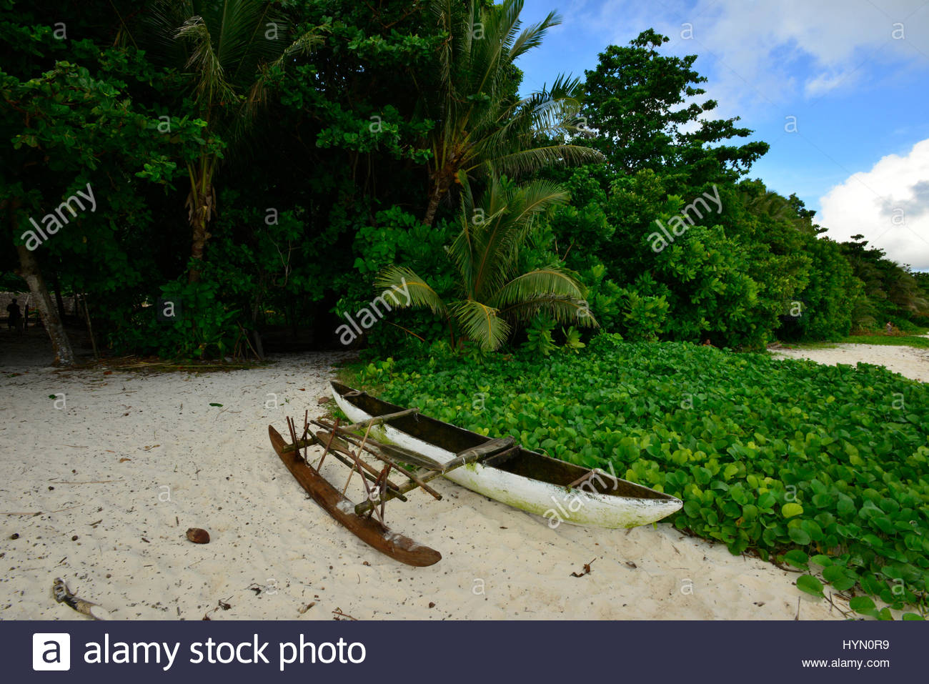 An outrigger fishing canoe on a beach on Tikopia Island. - Stock Image