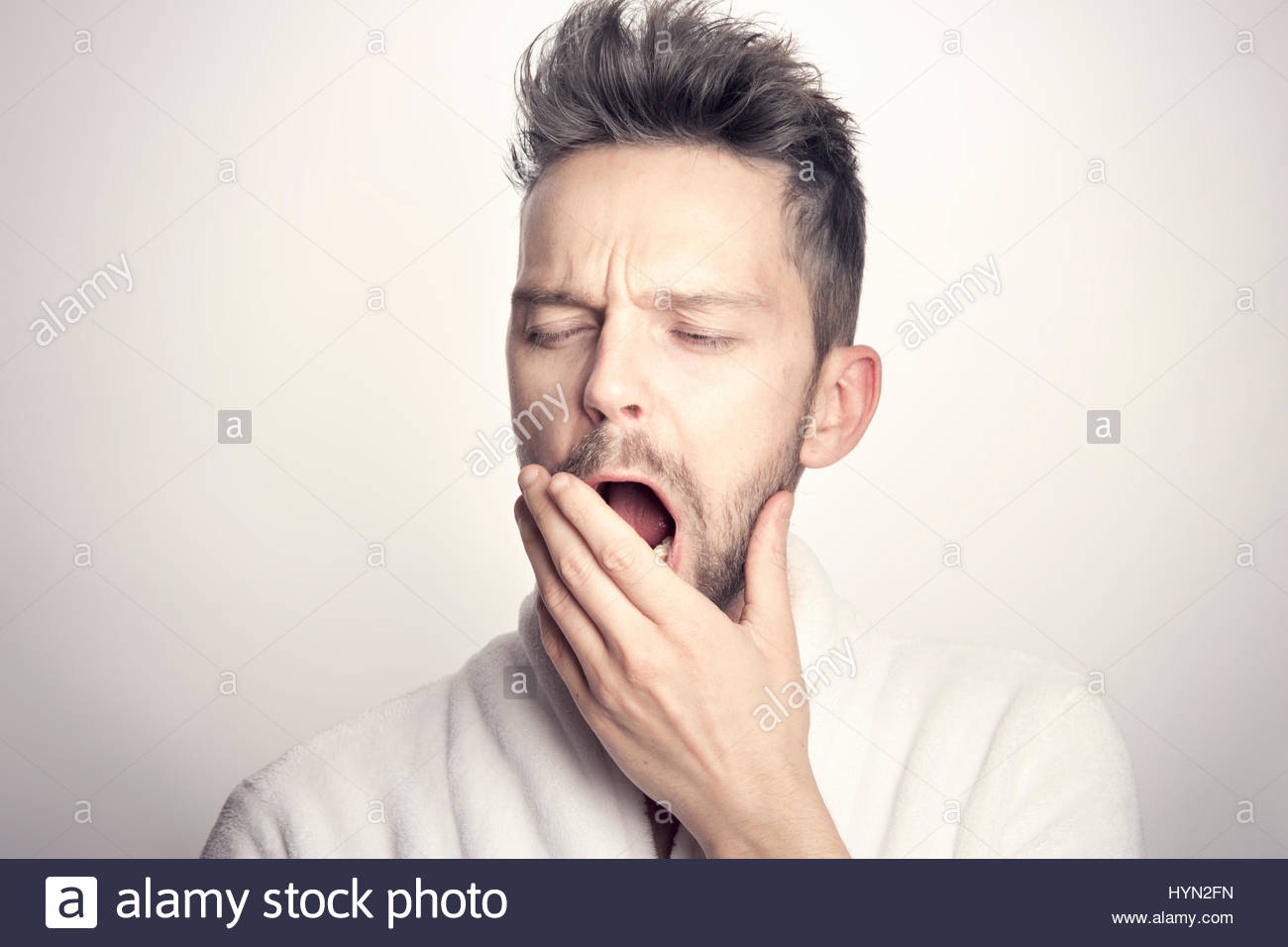 Man yawning with hand before mouth - Stock Image