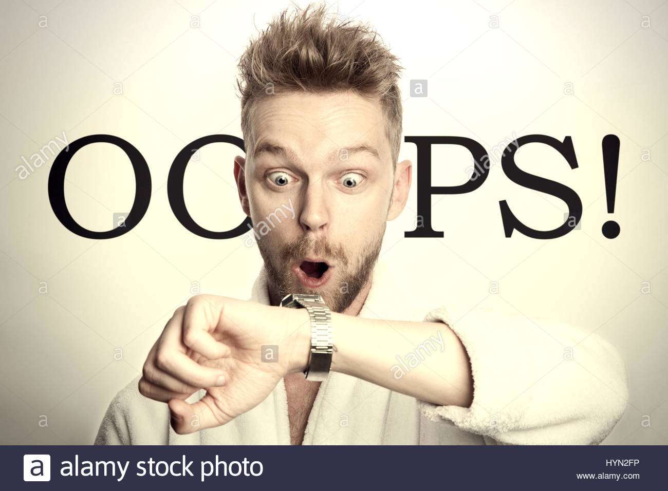 Man looking shocked at watch - Stock Image
