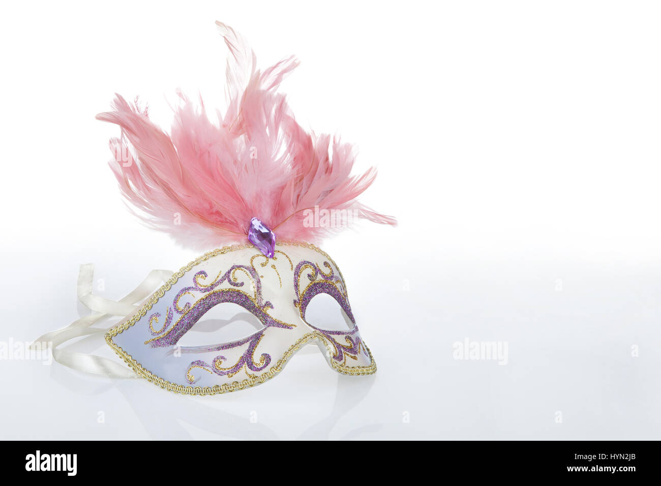 Beautiful carnival mask with pink feathers and a reflection, copy space on the right - Stock Image