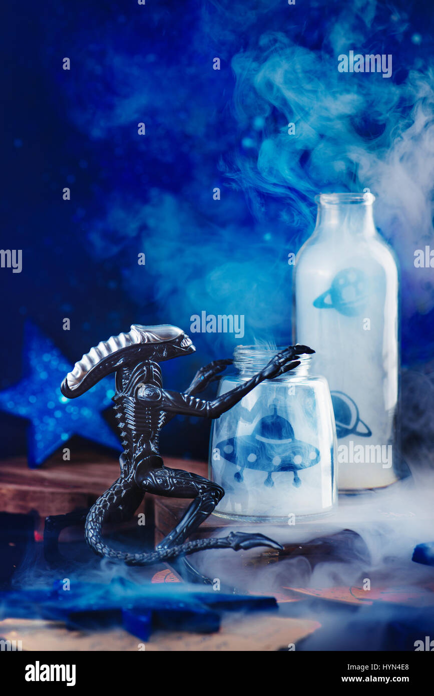 Toy alien with flying saucers and smoke on a dark background - Stock Image