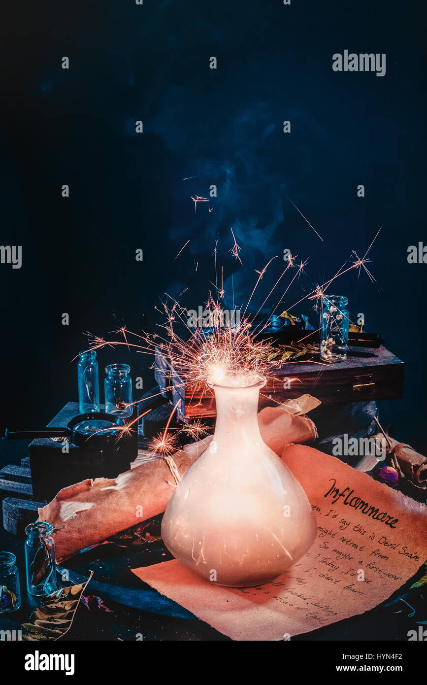 Magical potion with fiery sparks, ancient scroll and witchcraft items on a dark background - Stock Image
