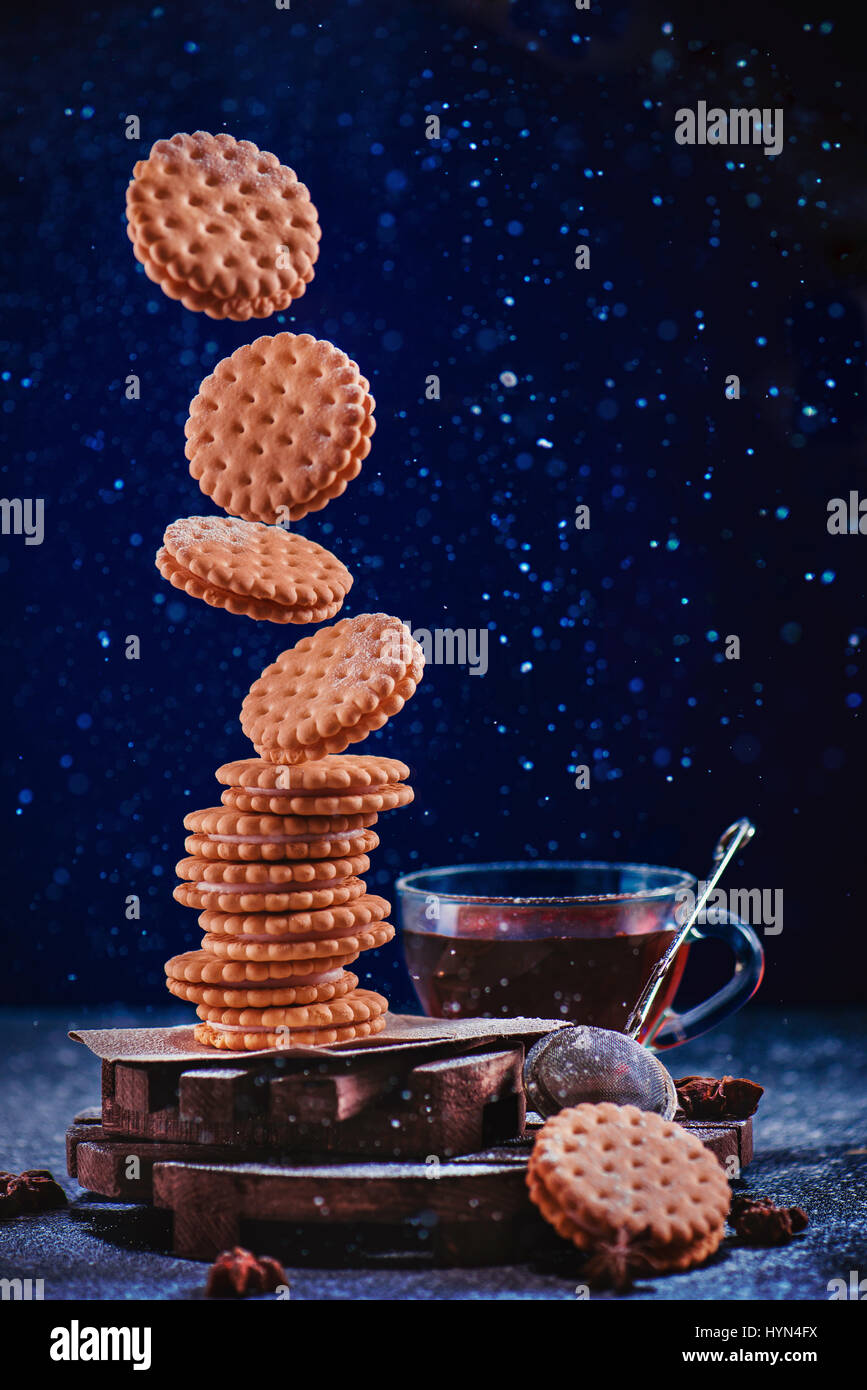 Dark food photo with a stack of flying cookies sprinkled with powdered sugar - Stock Image